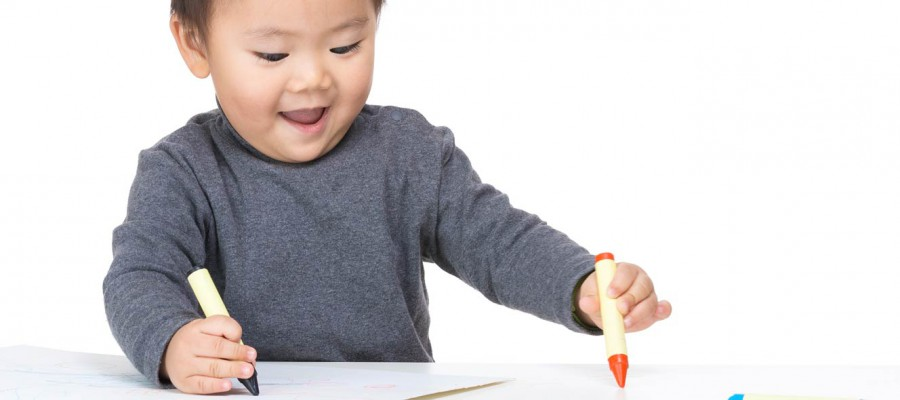 young boy colouring with crayons