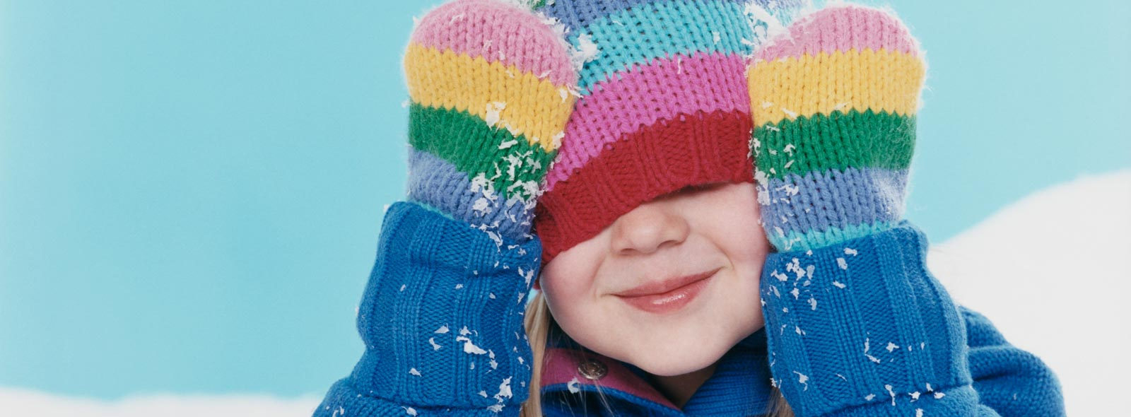 young girl smiling wearing mittens with hands on head